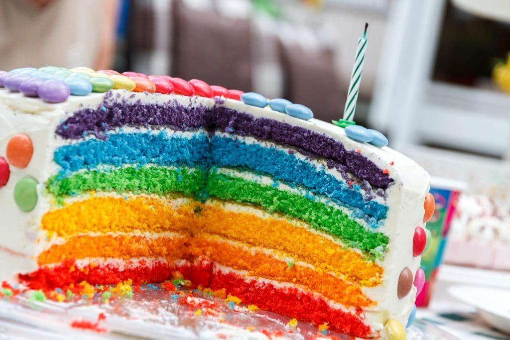 sliced rainbow cake with one candle