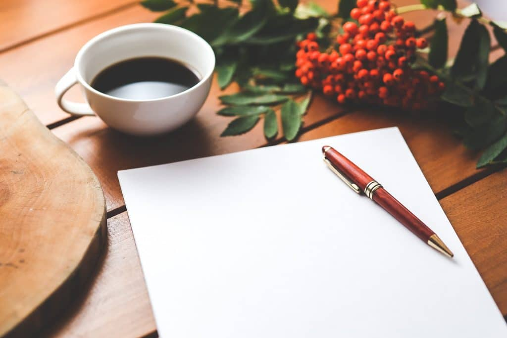 a piece of paper with pen and a cup of coffee