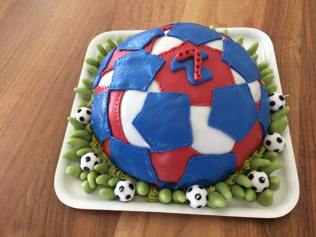 Cake that looks like a soccer ball with blue red and white colors