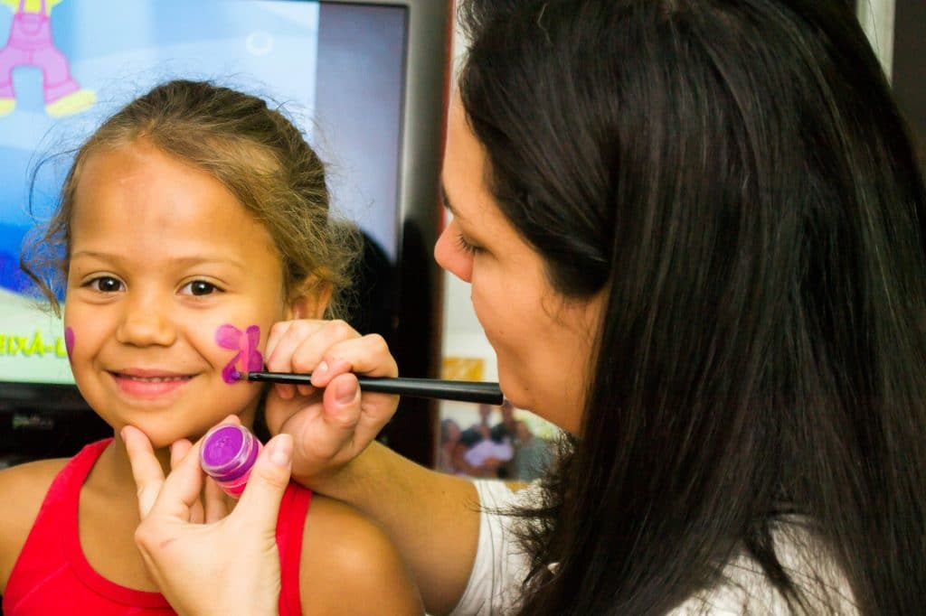 Woman putting make up on a little girl