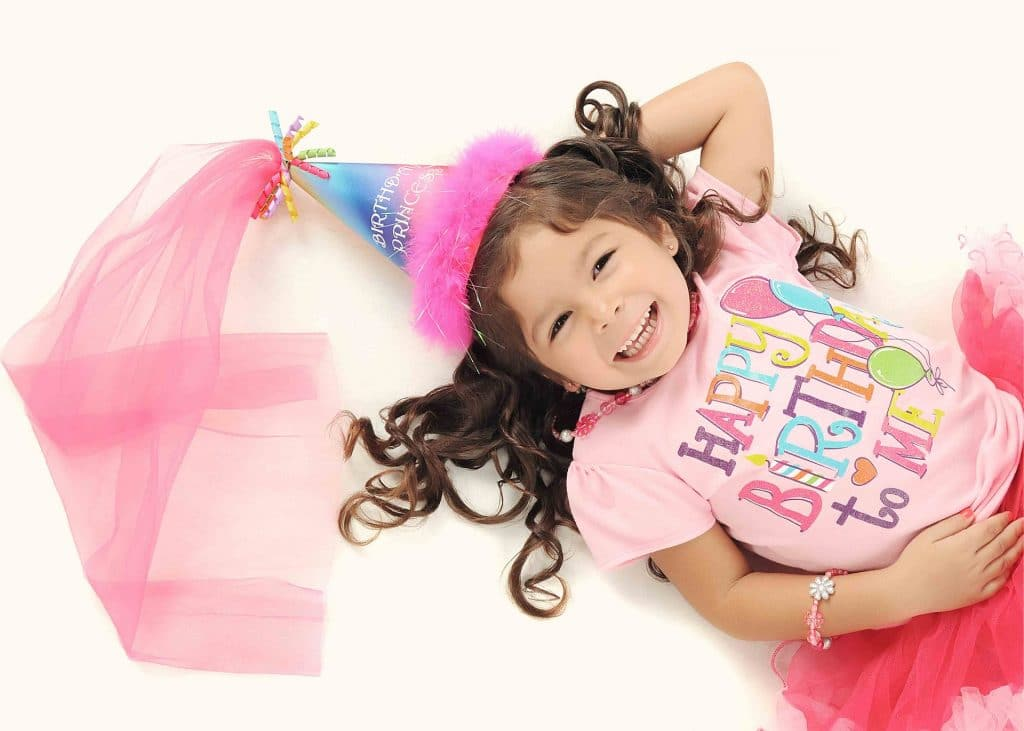 girl wearing pink blouse printed happy birthday to me and a pink cap