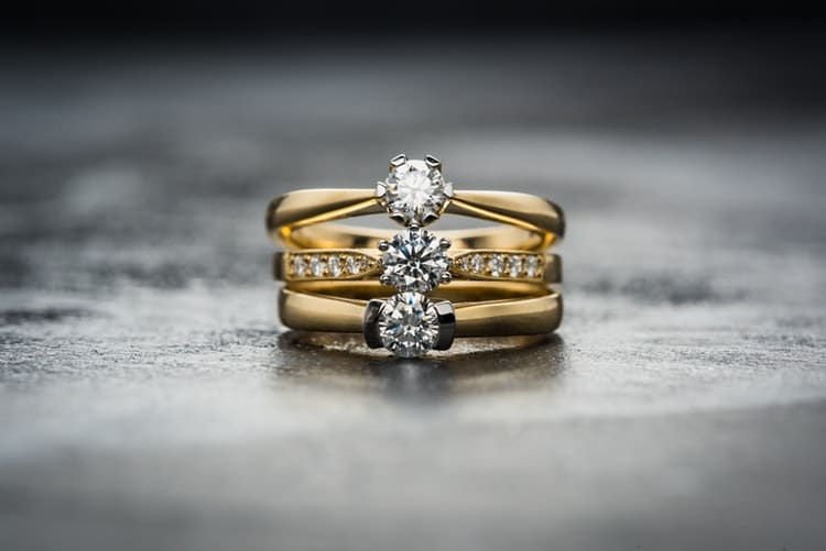 three gold rings with diamonds at the center