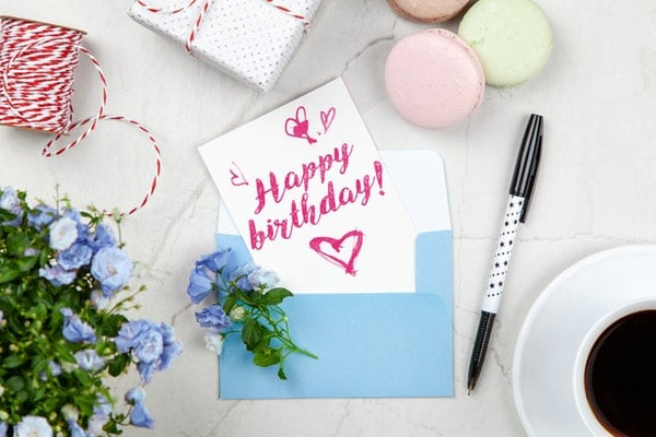 flowers and happy birthday card with blue envelope