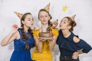 three teenage female friends blowing candles birthday cake
