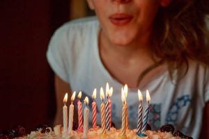 lady blowing candle on birthday cake