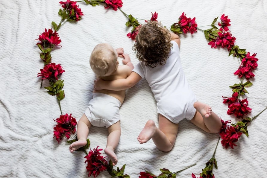 a baby with big sister on a bed with birthday wishes in a flower heart