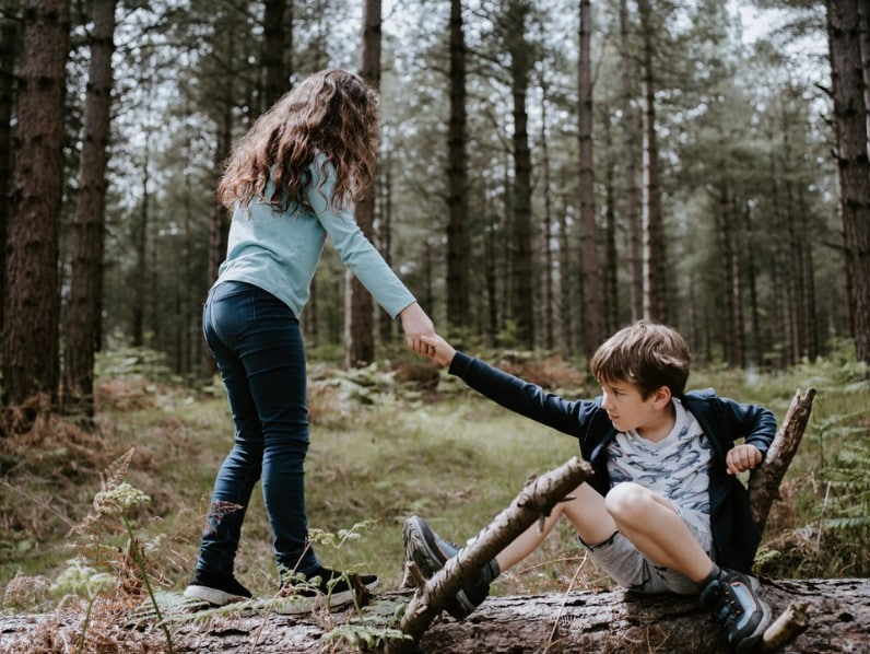 big sister helping her brother up off of a log, memories for a birthday wish